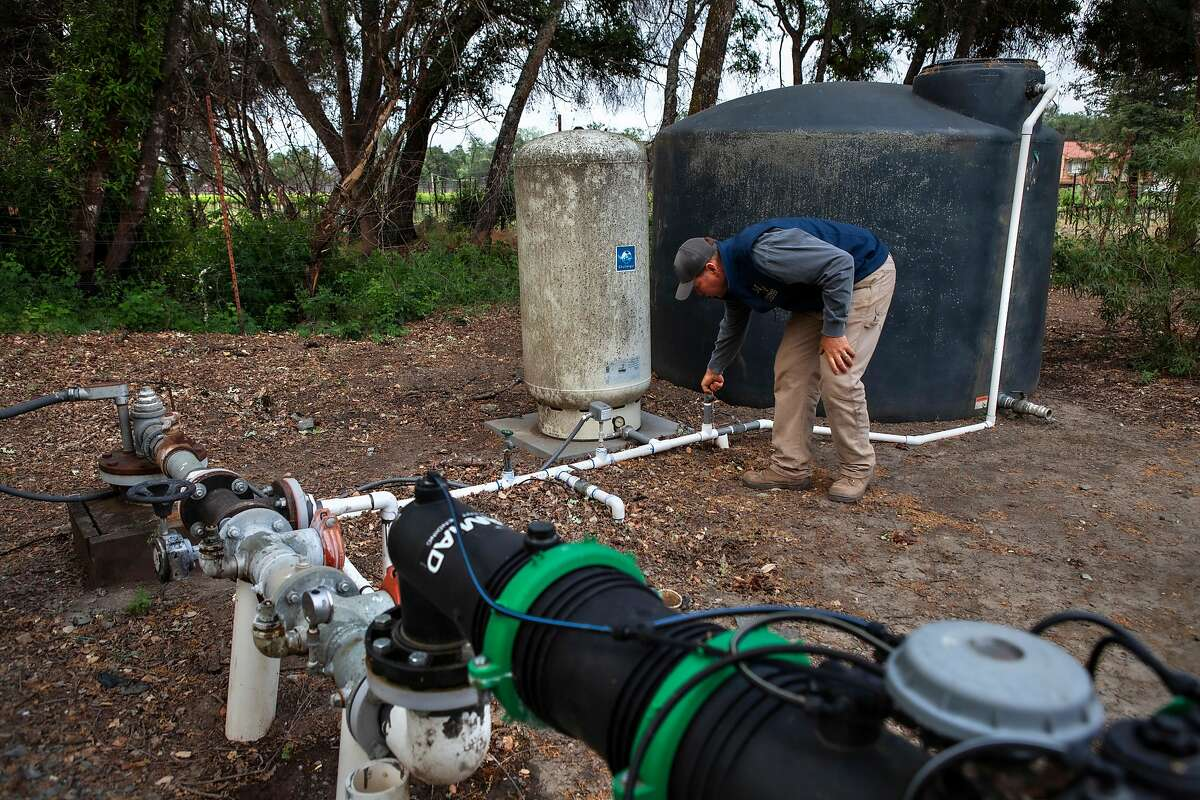 Bret Munselle, vineyard owner and manager of the Munselle Vineyards, checks to make sure the drip pipes are working in Geyserville, California May 6, 2021.
