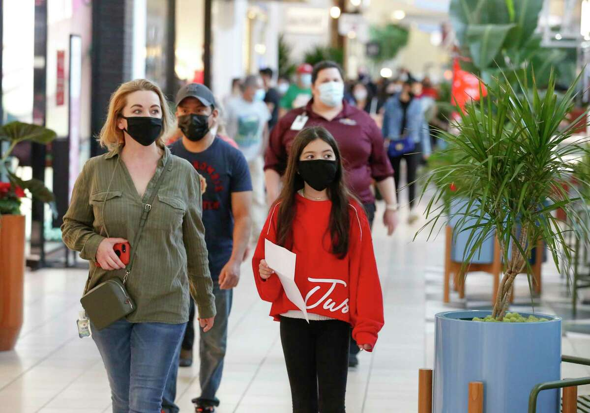 Susi Quintana and her daughter, Randi, 11, compete in a family scavenger hunt before doing their last minute Christmas shopping at Memorial City Mall Wednesday, Dec. 23, 2020, in Houston. The CDC altered its guidelines for what vaccinated people can safely do, saying fully vaccinated people can resume prepandemic activities without masks and social distancing.
