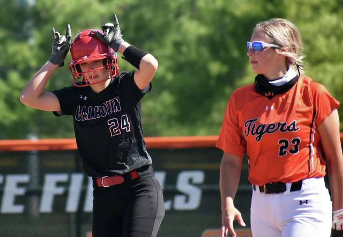 Calhoun's Lucy Kallal (left) signs back to the Warriors dugout after hitting a double in an April 30 game at Edwardsville while Tigers second baseman Lexi Gorniak walks from the base. Kallal had two more doubles Thursday in Calhoun's win at Greenfield.