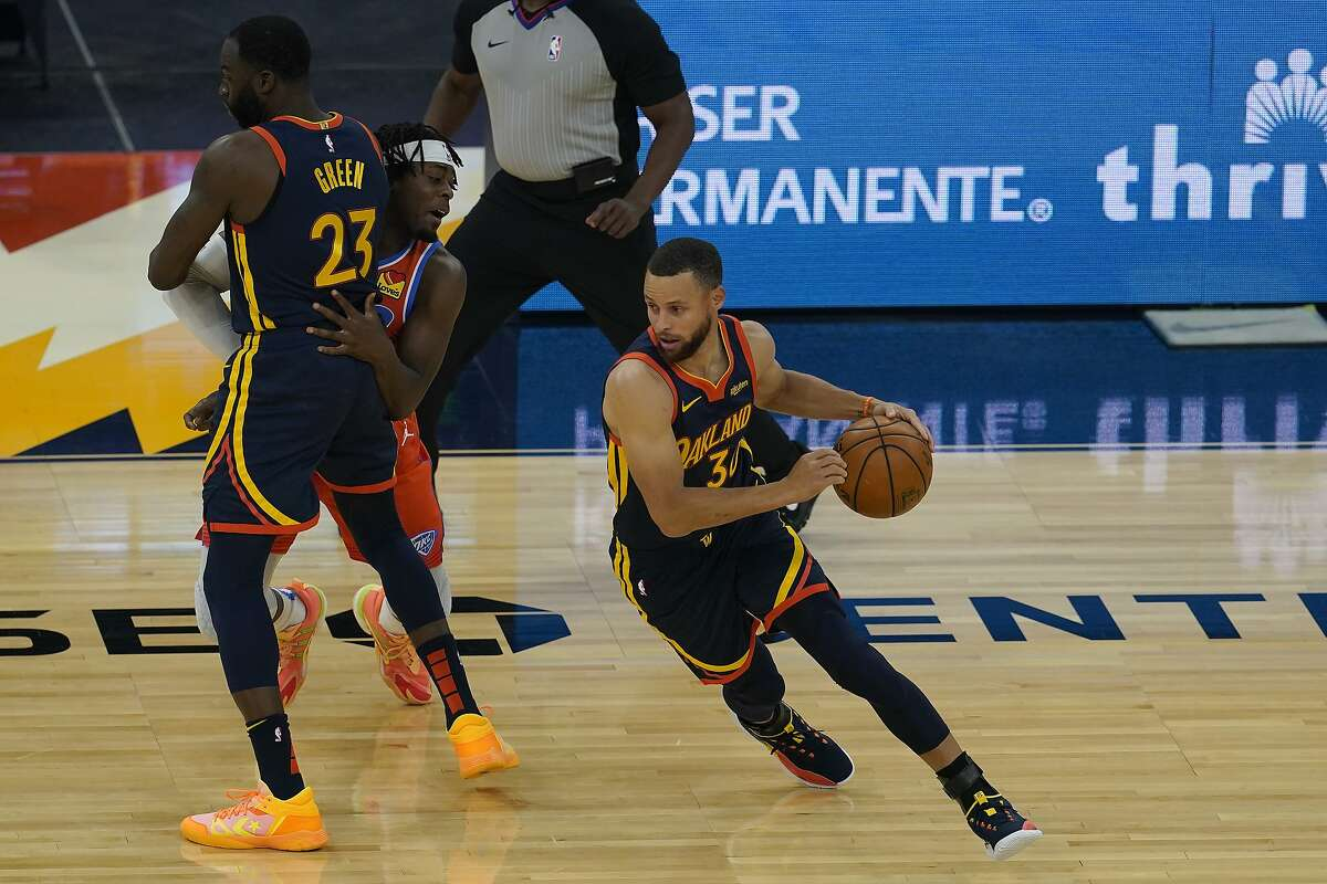 Golden State Warriors guard Stephen Curry, right, dribbles as forward Draymond Green (23) screens against the Oklahoma City Thunder's Luguentz Dort during an NBA basketball game in San Francisco, Thursday, May 6, 2021. (AP Photo/Jeff Chiu)