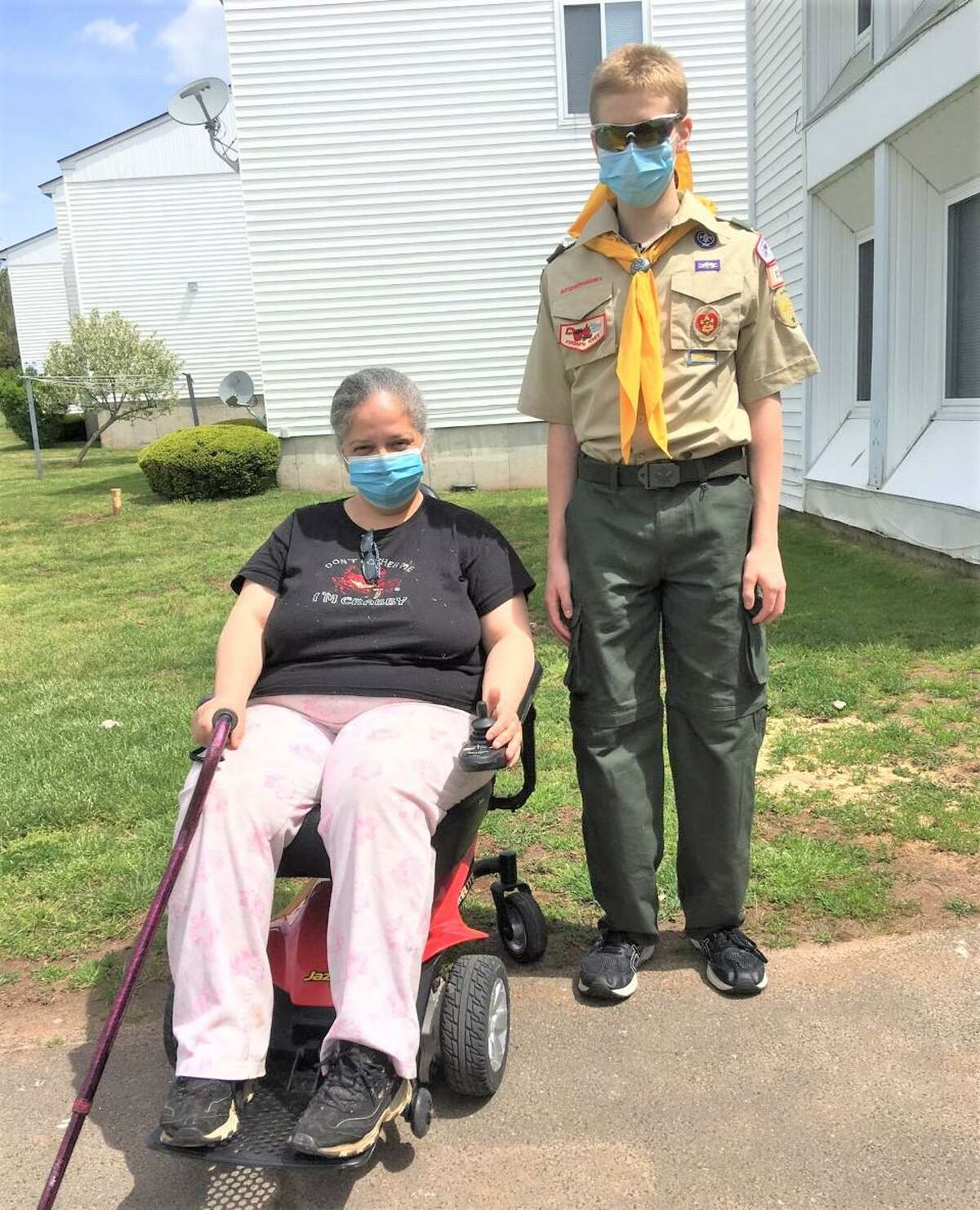 Middletown Boy Scout Michael Kline, 15, left, and Adela Santiago, right, are shown with the motorized wheelchair he purchased for her and delivered on Mother's Day.