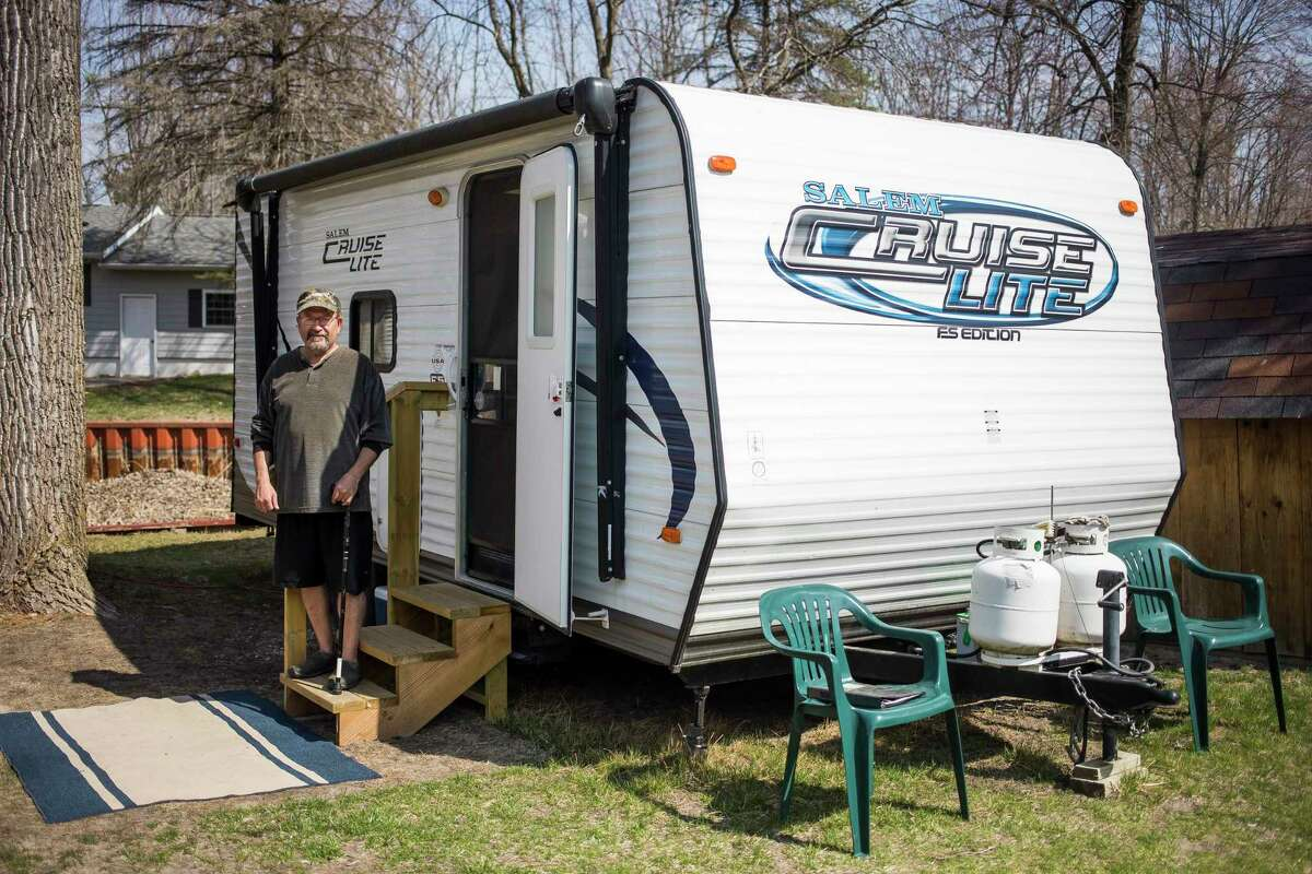 Bill Vasicek poses for a portrait Wednesday, April 7 next to the camper he lived in after his home in Hope was severely damaged in the flood. (Katy Kildee/kkildee@mdn.net)