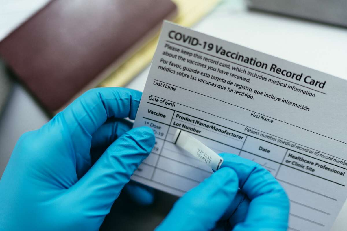 Medical worker placing a dose sticker on a COVID-19 Vaccination Record Card