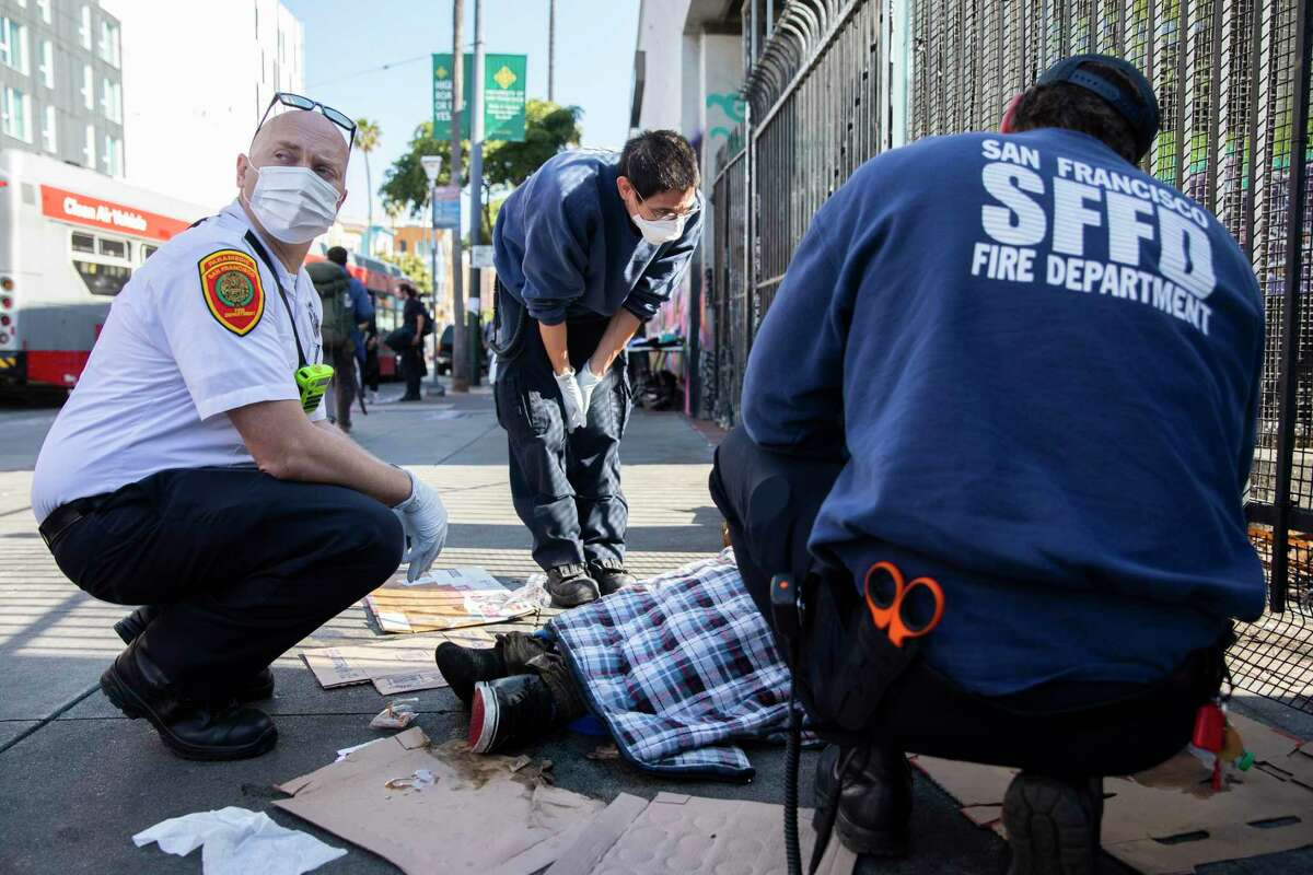 San Francisco paramedic Eddy Bird (left) joins two emergency medical technicians in assessing a homeless man in distress near 16th and Mission streets.