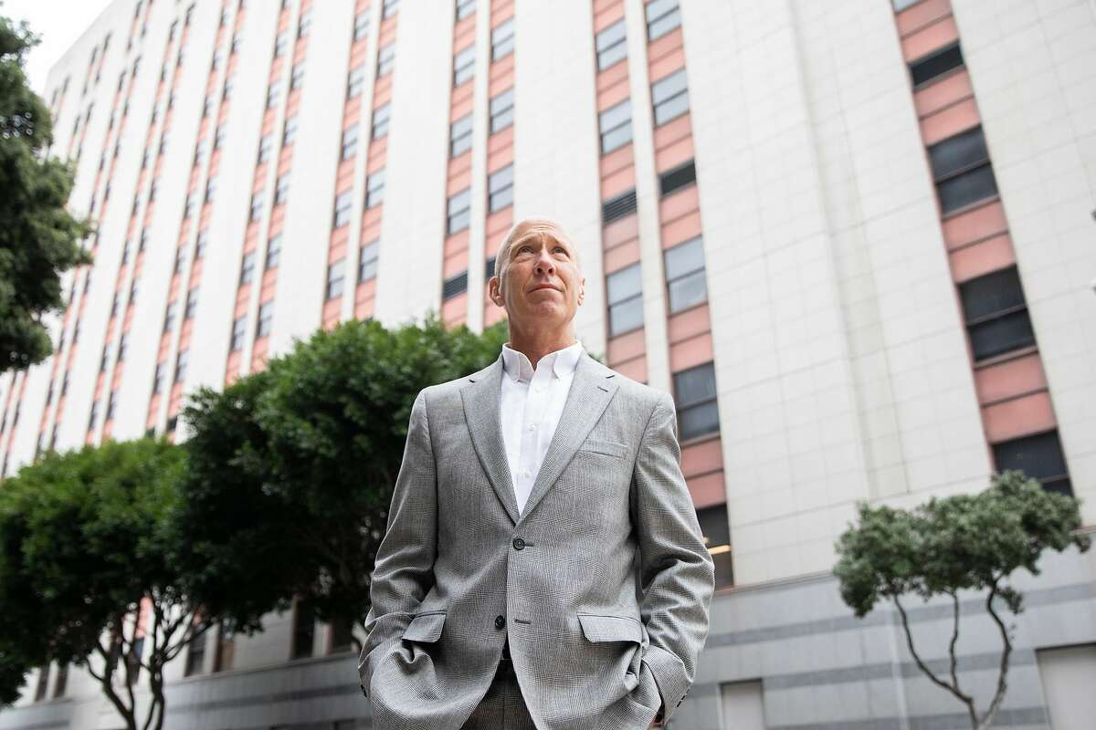 """Retired Judge Bill Hanrahan stands outside of the U.S. Immigration and Customs court building in San Francisco on May 14. The former managing judge of the San Francisco immigration court delivered a blistering exit interview after retiring from the system, saying the courts are run by a """"soul-crushing bureaucracy"""" that needs """"wholesale reform."""""""