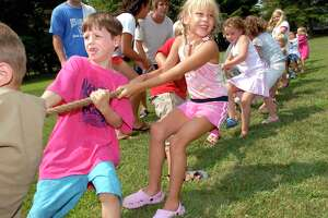 8-3-2007, GREENWICH CIVIC CENTER, OLD GREENWICH, Louis Werberg, 5, left, and Bianca Alberti, 7, center, pull the rope in a tug-of-war contest during Olympics Day at the Town of Greenwich's Kamp Kairphree, Friday morning at the Greenwich Civic Center in Old Greenwich. PHOTO/BOB LUCKEY Staff Photo Luckey,Bob