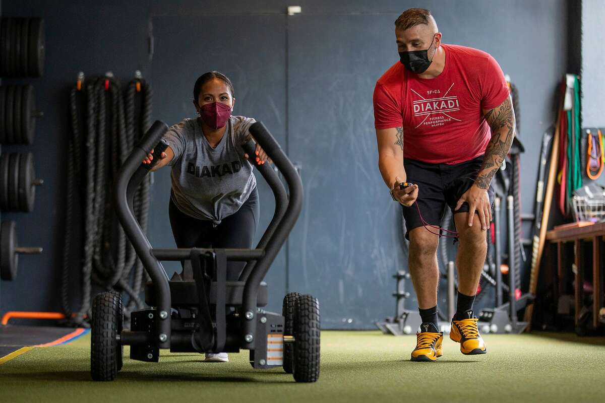 Tiana Dolorfino works out with trainer Tommy Armenta at DIAKADI fitness center on May 13, 2021, in San Francisco.