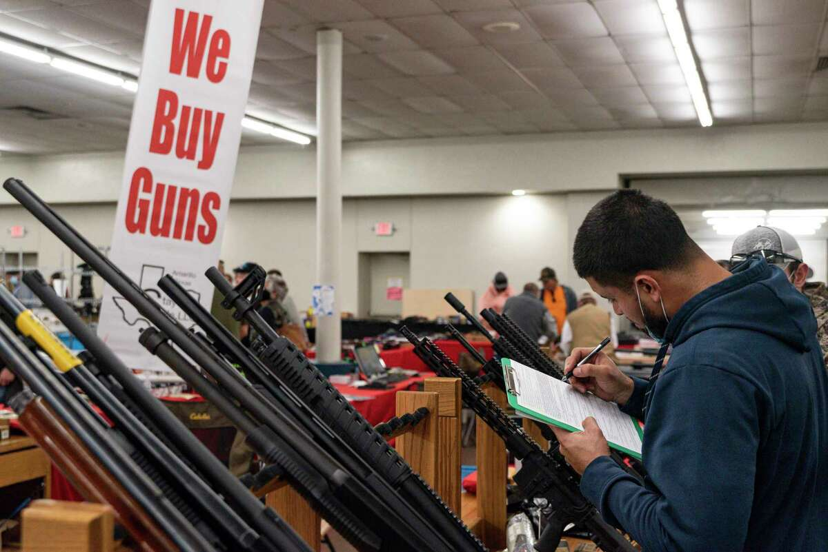 A man fills out paperwork to buy a firearm at a gun show in Odessa. A reader asks the public not to fear responsible gun ownership.