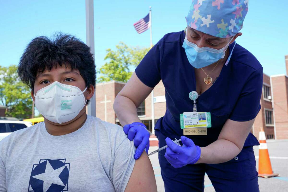 Registered Nurse Jennifer Reyes inoculates Andres Clara, 12, with the first dose of the Pfizer COVID-19 vaccine at the Mount Sinai South Nassau Vaxmobile parked at the De La Salle School, Friday, May 14, 2021, in Freeport, N.Y. (AP Photo/Mary Altaffer)