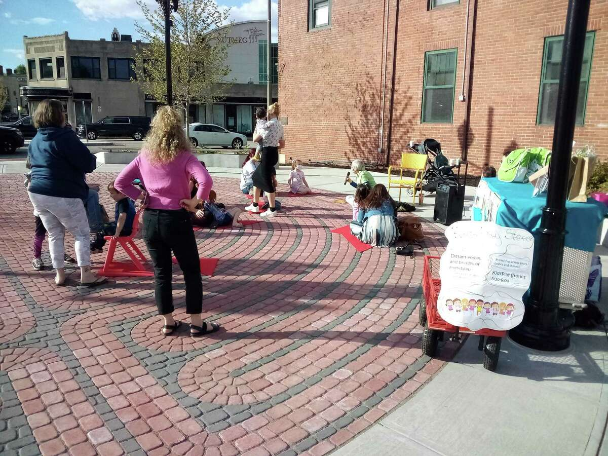 The farmers market at Franklin Square is held from 4-7 p.m. on Thursdays. Above, families hear a story reading with KidsPlay Children's Museum.