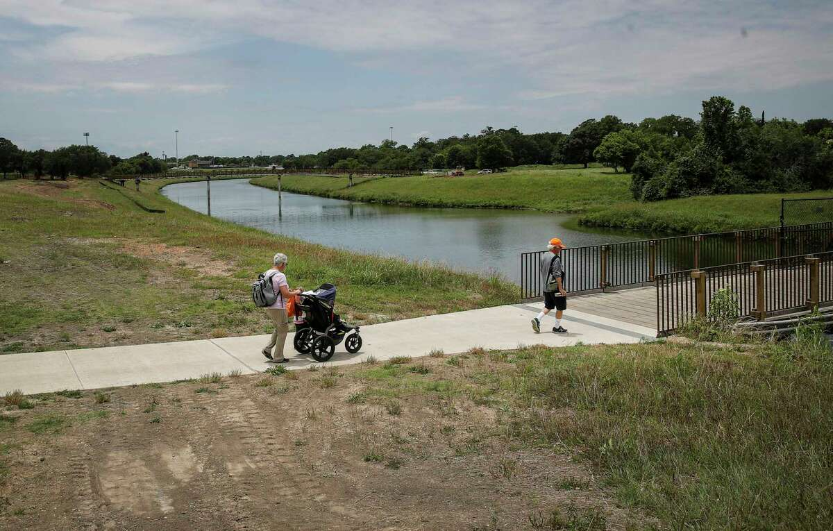 Tim Touzel, right, and his wife Marion, left, walk with their grandchildren Isaac, 2, and Sammy, 7 months, along Sims Bayou on May 14, 2021, near Glenbrook Park in Houston. Local officials broke ground Thursday on a 1.1-mile segment of a hike-and-bike trail connecting the park to a trail east of Interstate 45 along the Houston Botanic Garden site. The pair said they had previously volunteered at the garden, and that they had come to spend time with their grandchildren.