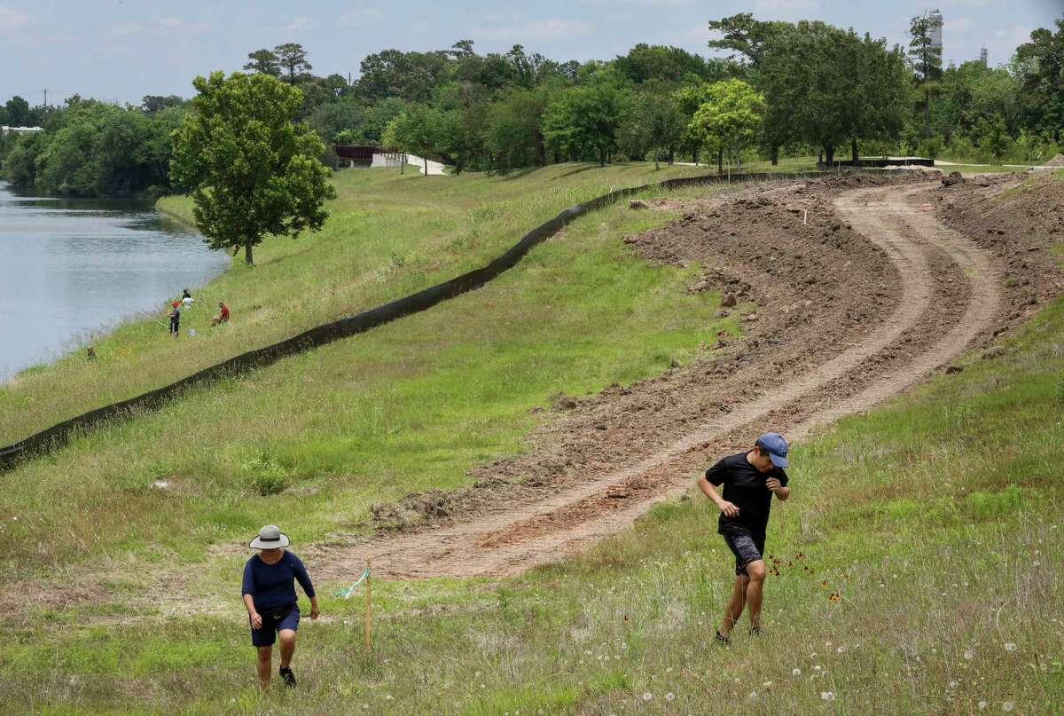 Juan Aparicio, right, and his wife Frine Aparacio jog along Sims Bayou on May 14, 2021, near Glenbrook Park in Houston. Local officials broke ground Thursday on a 1.1-mile segment of a hike-and-bike trail connecting the park to a trail east of Interstate 45 along the Houston Botanic Garden site. Juan Aparicio said he was
