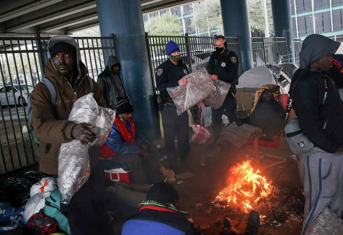 Houston Police officers Kenneth Bigger, center, and Aaron Day, center-right, hand out blankets to people as a winter storm continues to hit the area Tuesday, Feb. 16, 2021.