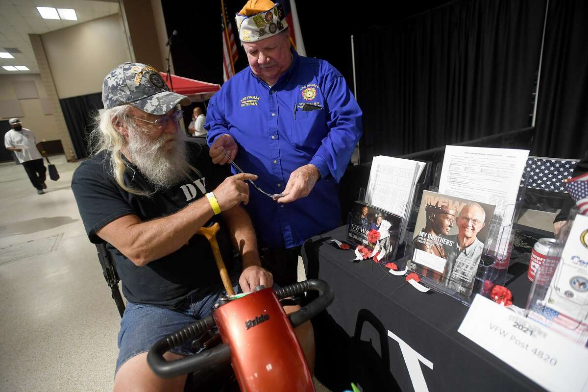 VFW Post 4820 member Jim Rose hands a specialty Navy dog tag for veteran Robert Sanford during Southeast Texas Stand Down 2021 in Port Arthur Friday. Numerouse veterans organizations as well as other health and community action services filled the Bob A. Bowers Civic Center for the event, which aims to connect veterans and the homeless with needed resources. A fall event will be held in Beaumont. Photo made Friday, May 14, 2021 Kim Brent/The Enterprise