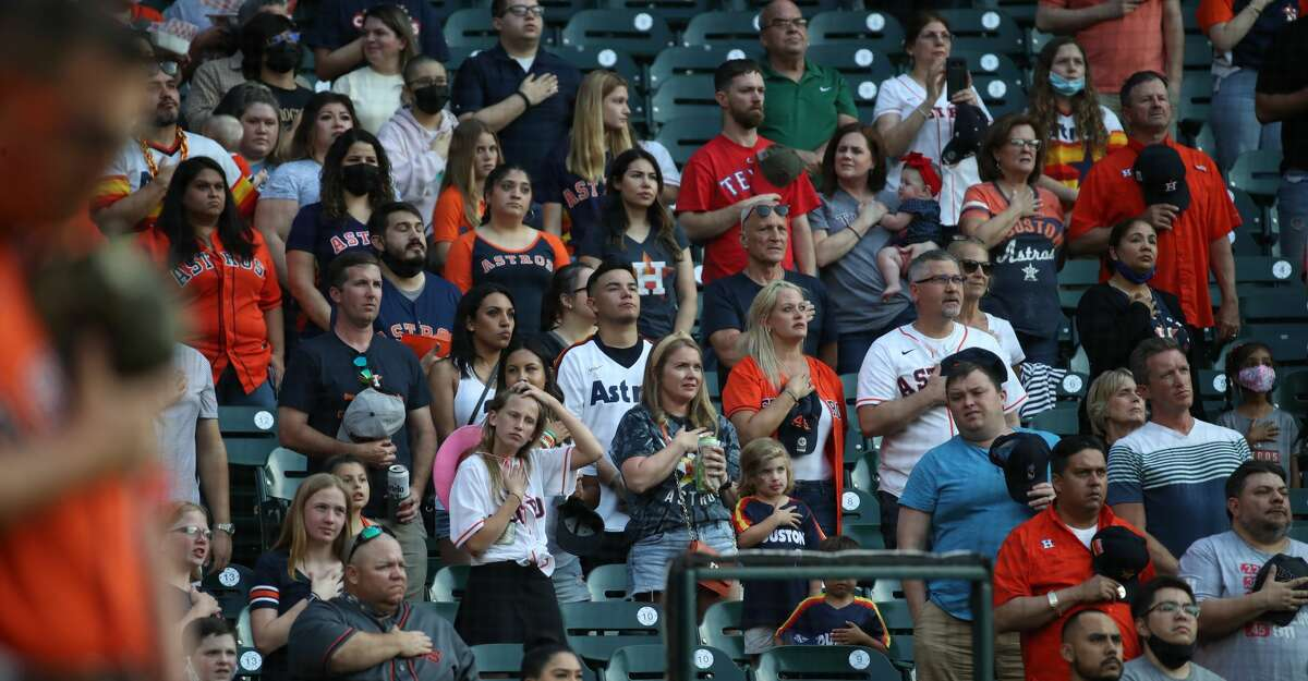 Fans listen to the national anthem before a game between the Houston Astros and the Texas Rangers on Friday, May 14, 2021, at Minute Maid Park in Houston.