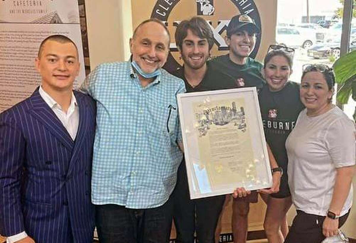 """Cleburne Cafeteria owner and operator George Mickelis holds the official City of Houston proclamation declaring May 8, 2021 has """"Cleburne Cafeteria Day in the City of Houston"""" in honor of the landmark local cafeteria's 80th anniversary. To George's right is city representative Bret Hightower. To George's left are his children Anthony, Matthew and Athena and his girlfriend Tina."""