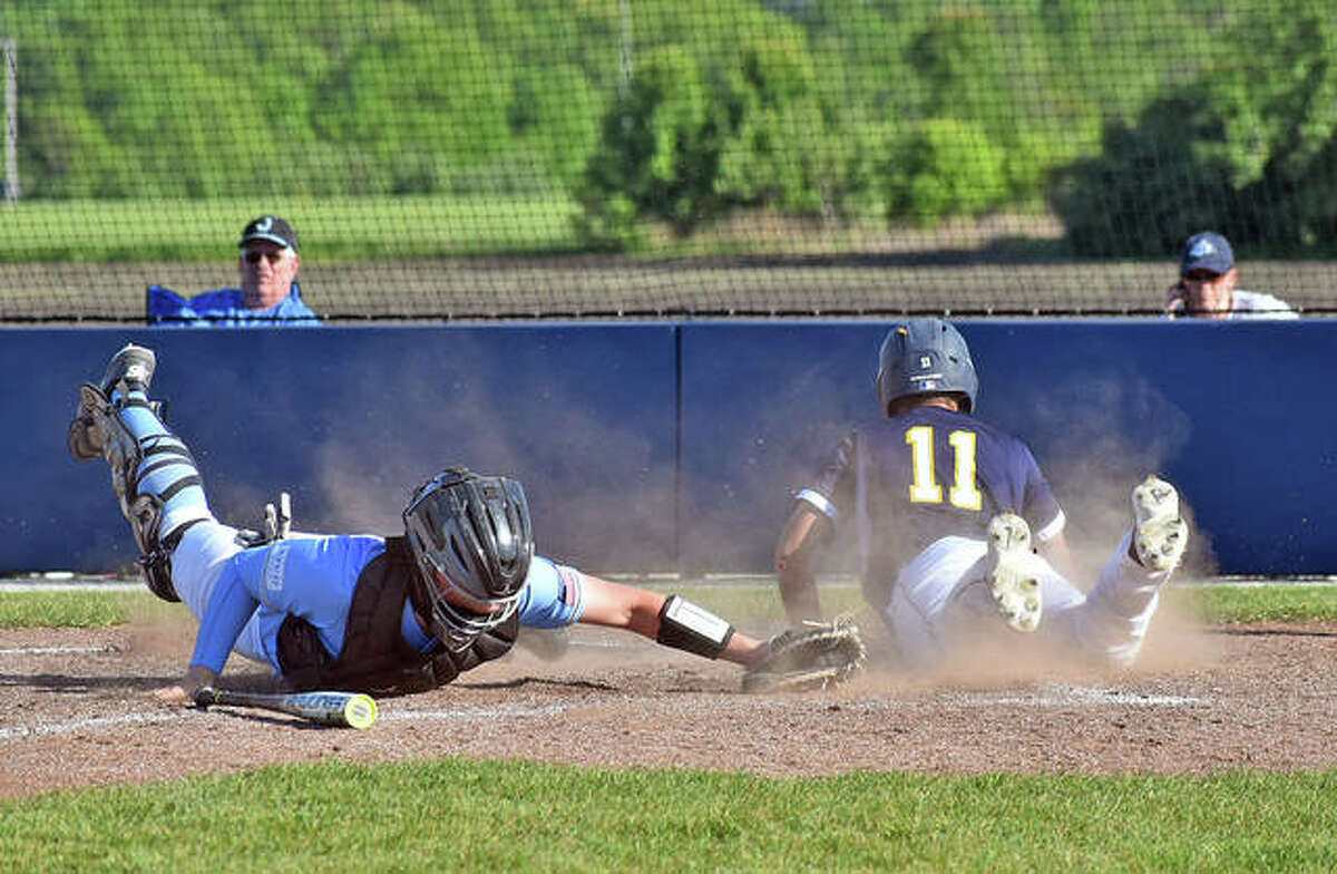 Father McGivney's AJ Sutberry slides safely across home plate just past the tag of Jersey catcher CJ Brunaugh during Friday's game in Glen Carbon.