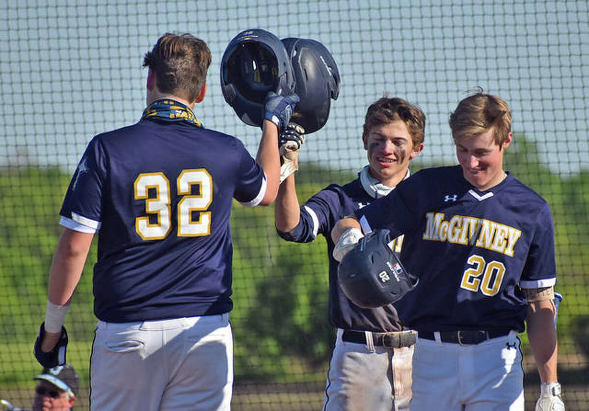 Father McGivney's Gabe Smith, left, is greeted by Austin Callovini, center, and Daniel Gierer after hitting a two-run homer in the third inning.