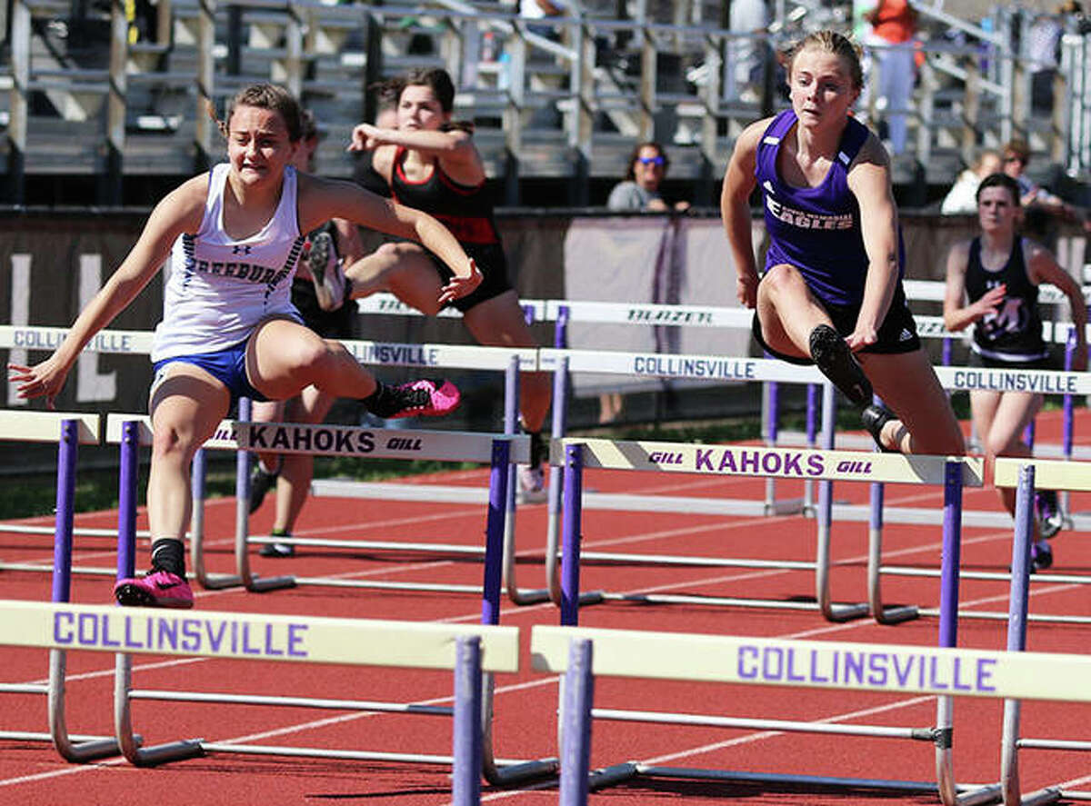 CM sophomore Isabella Dugger (right) follows Freeburg senior Megan Weilmuenster (left) over a hurdle midway through their 100-meter hurdles race Friday at the Collinsville Invite. Dugger finished second behind Weilmuenster.