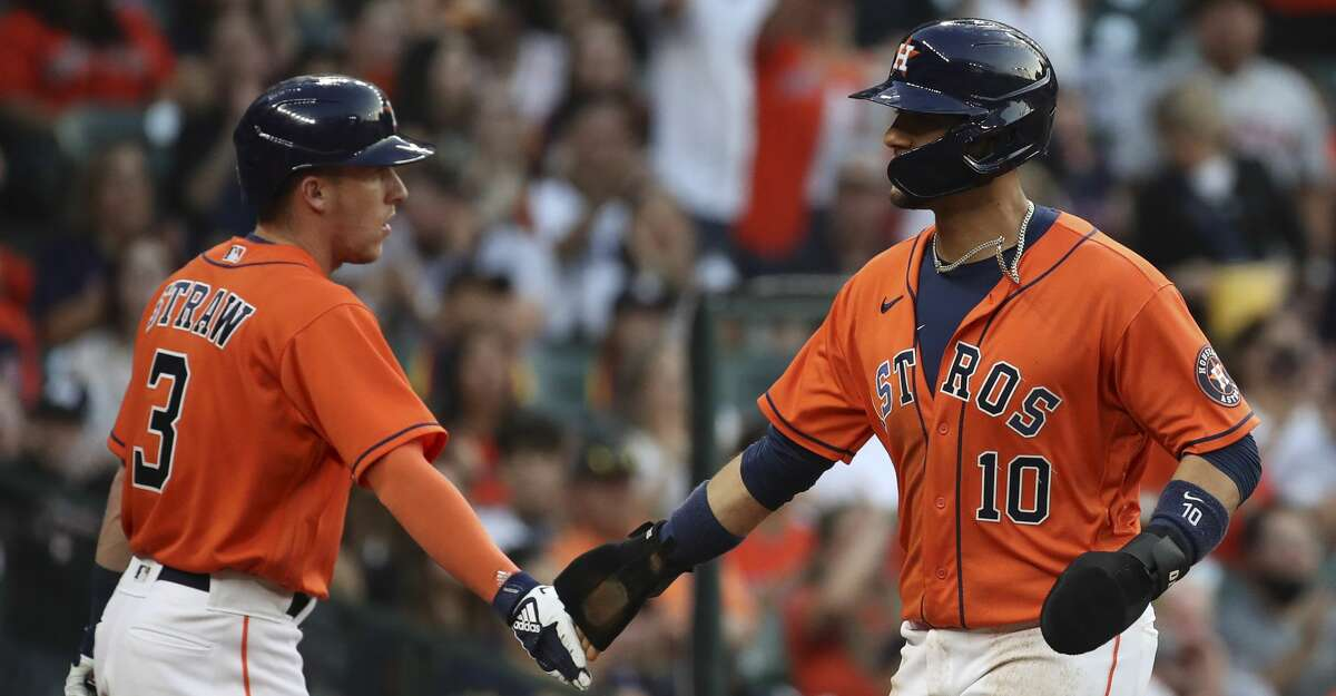 Houston Astros first baseman Yuli Gurriel (10) high fives center fielder Myles Straw (3) as he scores on a single by right fielder Kyle Tucker (30) during the second inning of an MLB game Friday, May 14, 2021, at Minute Maid Park in Houston.