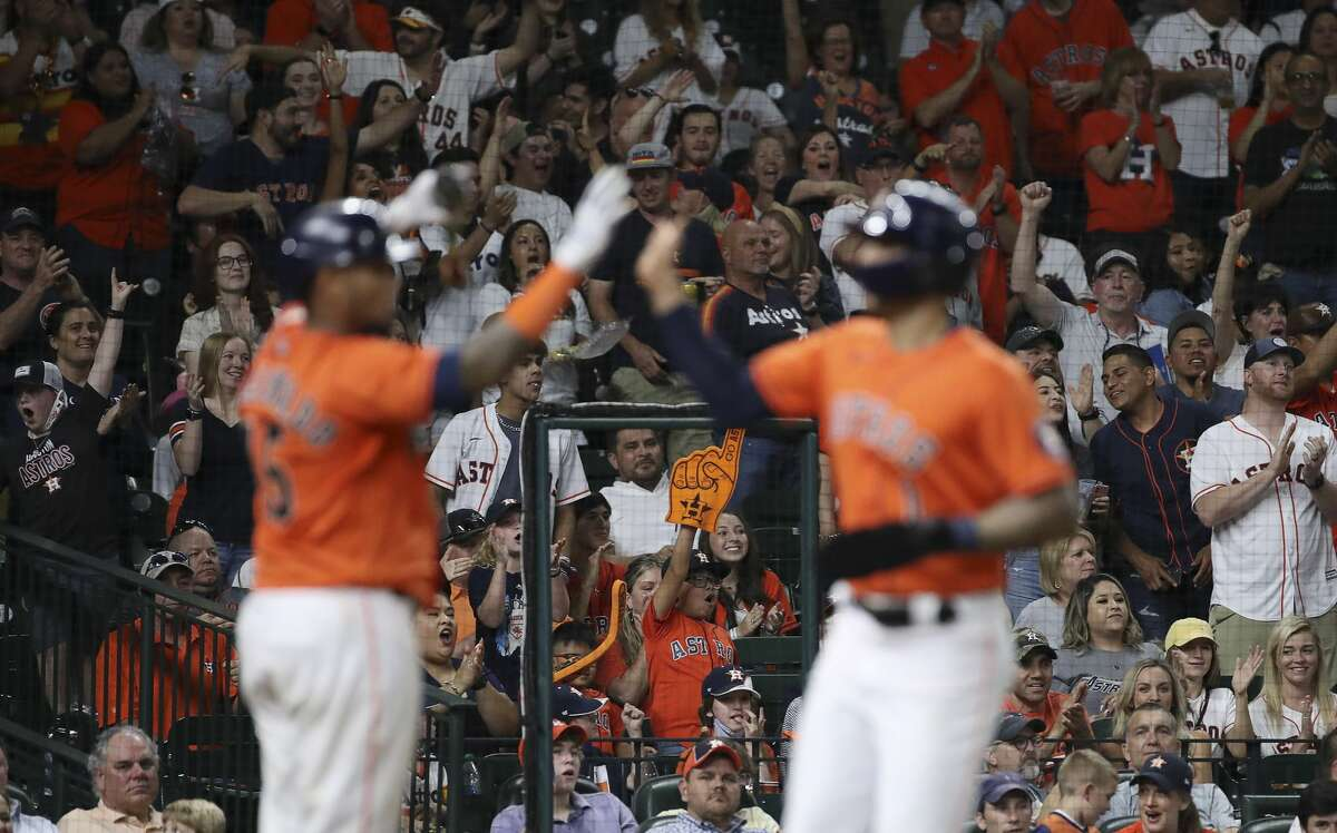 Fans cheer as Houston Astros shortstop Carlos Correa (1) high-fives catcher Martin Maldonado (15) after he scored on a single by center fielder Myles Straw (3) during the fifth inning of an MLB game Friday, May 14, 2021, at Minute Maid Park in Houston.