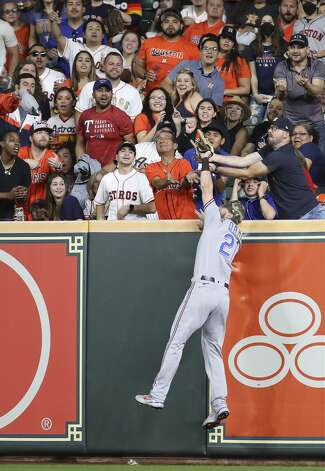 Texas Rangers right fielder David Dahl (21) reaches over the top of the outfield wall to make the catch to get out Houston Astros right fielder Chas McCormick (20) during the seventh inning of an MLB game Friday, May 14, 2021, at Minute Maid Park in Houston. Photo: Jon Shapley/Staff Photographer / © 2021 Houston Chronicle