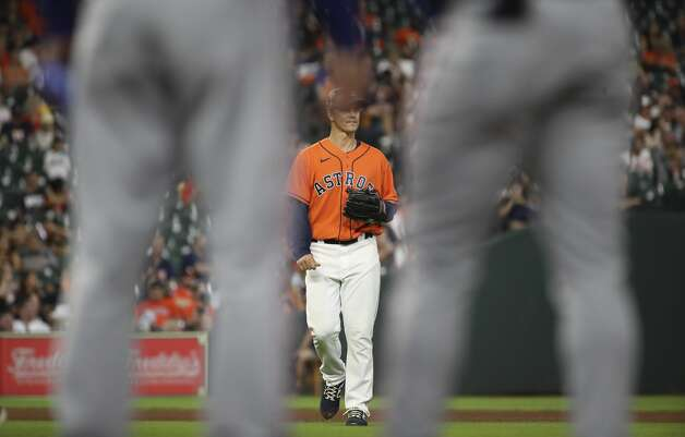 Houston Astros starting pitcher Zack Greinke (21), framed by Texas Rangers center fielder Adolis Garcia (53) and first base coach Corey Ragsdale (43), watches the outfield after a sacrifice fly from Texas Rangers designated hitter Khris Davis (4) brought in second baseman Nick Solak (15) during the fourth inning of an MLB game Friday, May 14, 2021, at Minute Maid Park in Houston. Photo: Jon Shapley/Staff Photographer / © 2021 Houston Chronicle