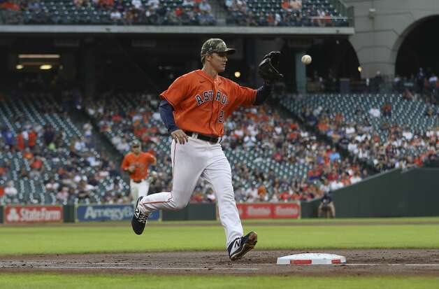 Houston Astros starting pitcher Zack Greinke (21) makes the catch from first baseman Yuli Gurriel (10), beating Texas Rangers right fielder David Dahl (21) to first for the third out during the second inning of an MLB game Friday, May 14, 2021, at Minute Maid Park in Houston. Photo: Jon Shapley/Staff Photographer / © 2021 Houston Chronicle