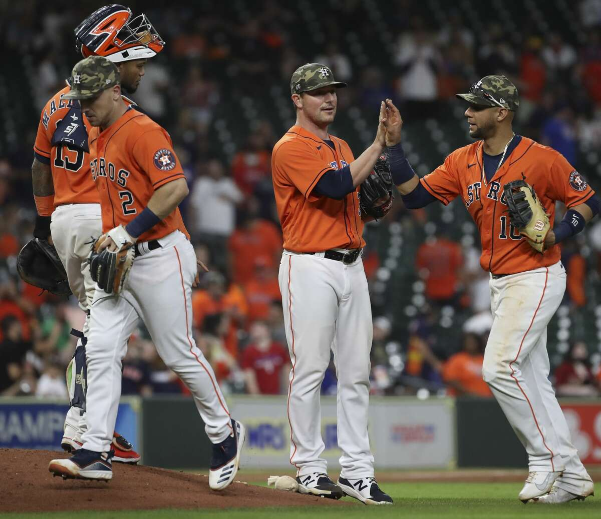Houston Astros catcher Martin Maldonado (15), third baseman Alex Bregman (2), relief pitcher Joe Smith (38) and first baseman Yuli Gurriel (10) celebrate after the Houston Astros beat the Texas Rangers during an MLB game Friday, May 14, 2021, at Minute Maid Park in Houston.
