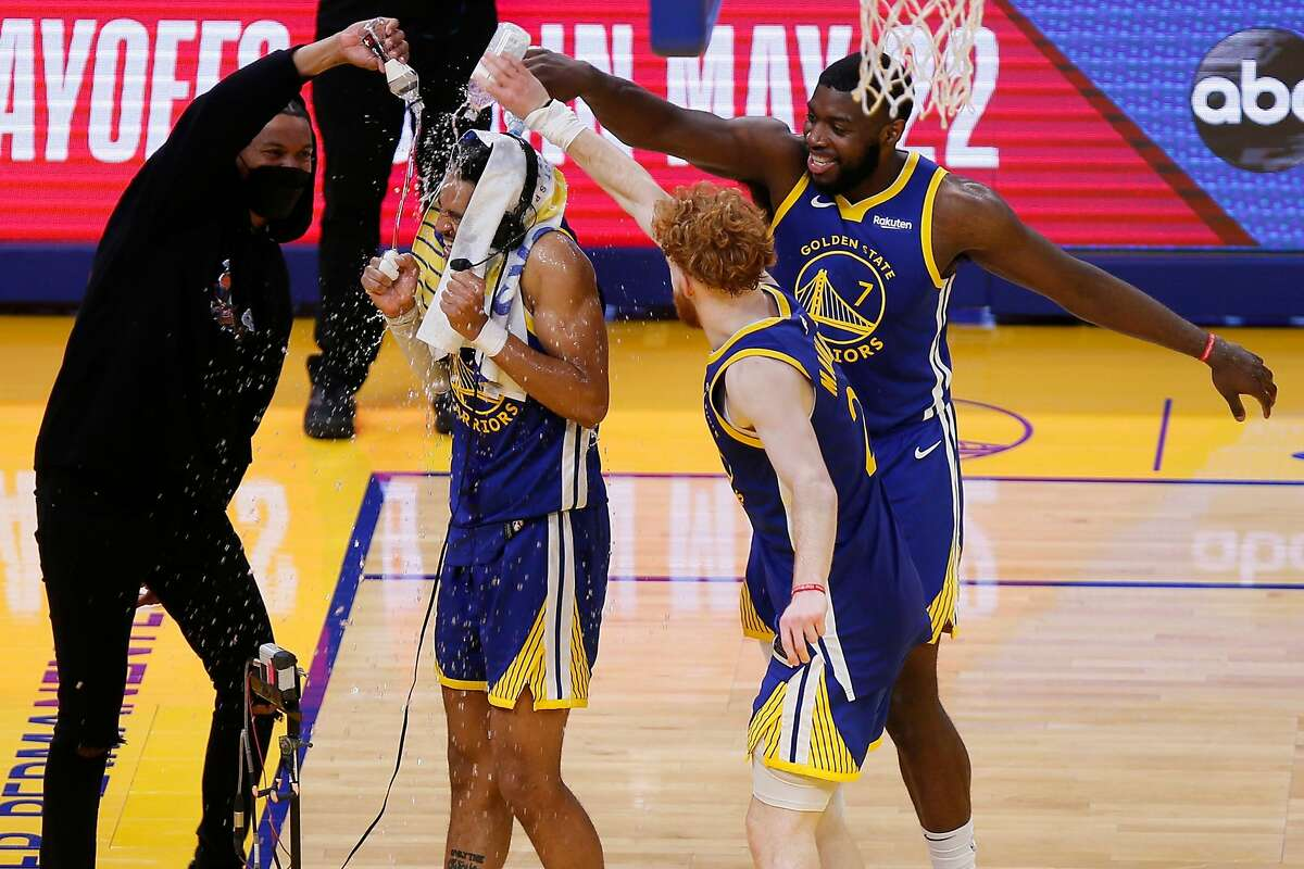 Jordan Poole gets showered by water bottles by his Warriors teammates after scoring 38 points Friday night.