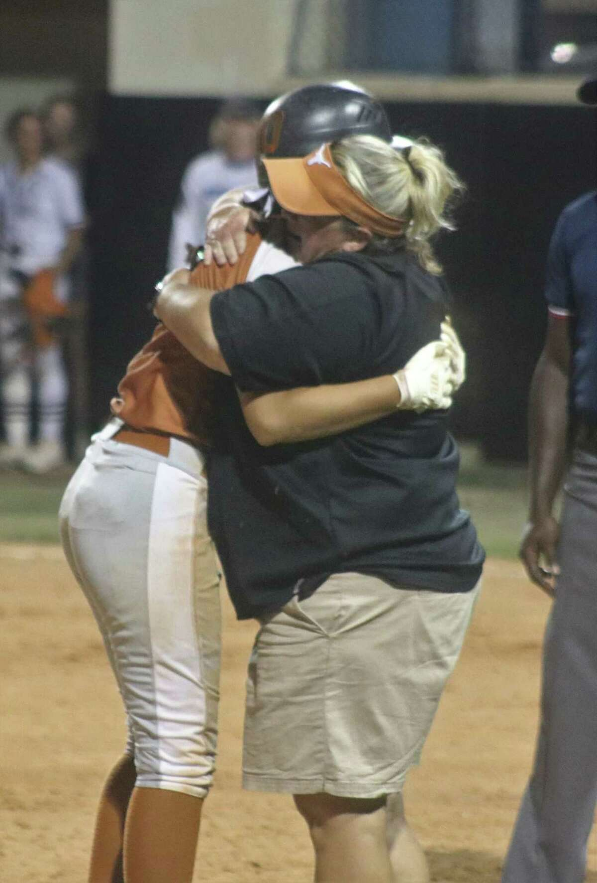 Dobie head coach Robin Rackley hugs Yessenia Pena after Pena launched an eighth-inning fly ball that sailed over the left fielder, getting Pena to third and getting the burnt orange within 3-2, but no closer.