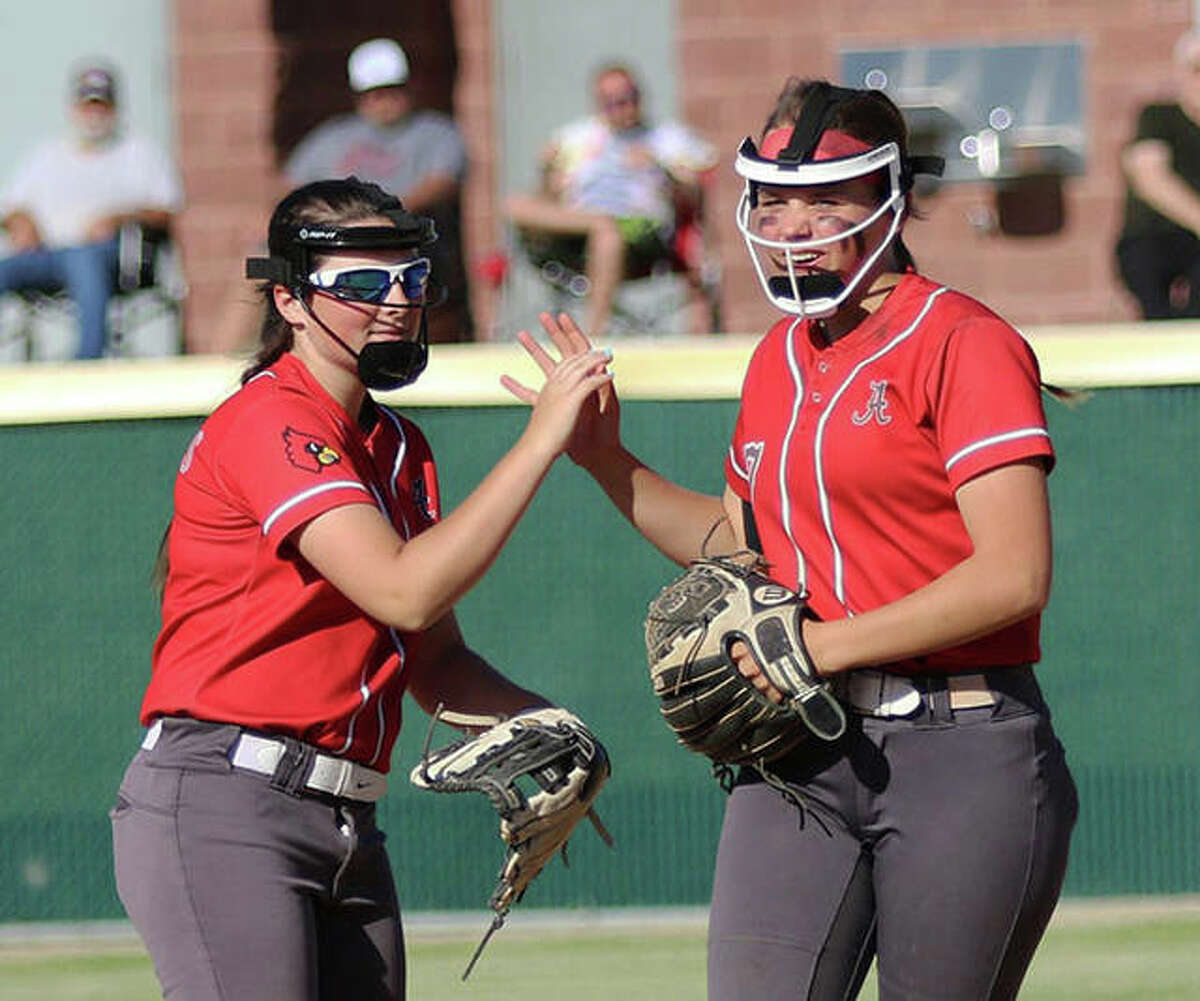Alton shortstop Alissa Sauls (right) is congratulated by third baseman Audrey Evola after Sauls made a big defensive play in Friday's SWC win over Belleville West in Godfrey