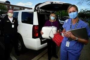 Norwalk Health Department volunteers Jim Brubaker, Linda Scanlon and Lindsay Lawlor, return from the city's bedbound vaccination program Thursday, May 12, 2021, in Norwalk, Conn. The volunteers administer vaccines to elderly and disabled Norwalk residents who are homebound.