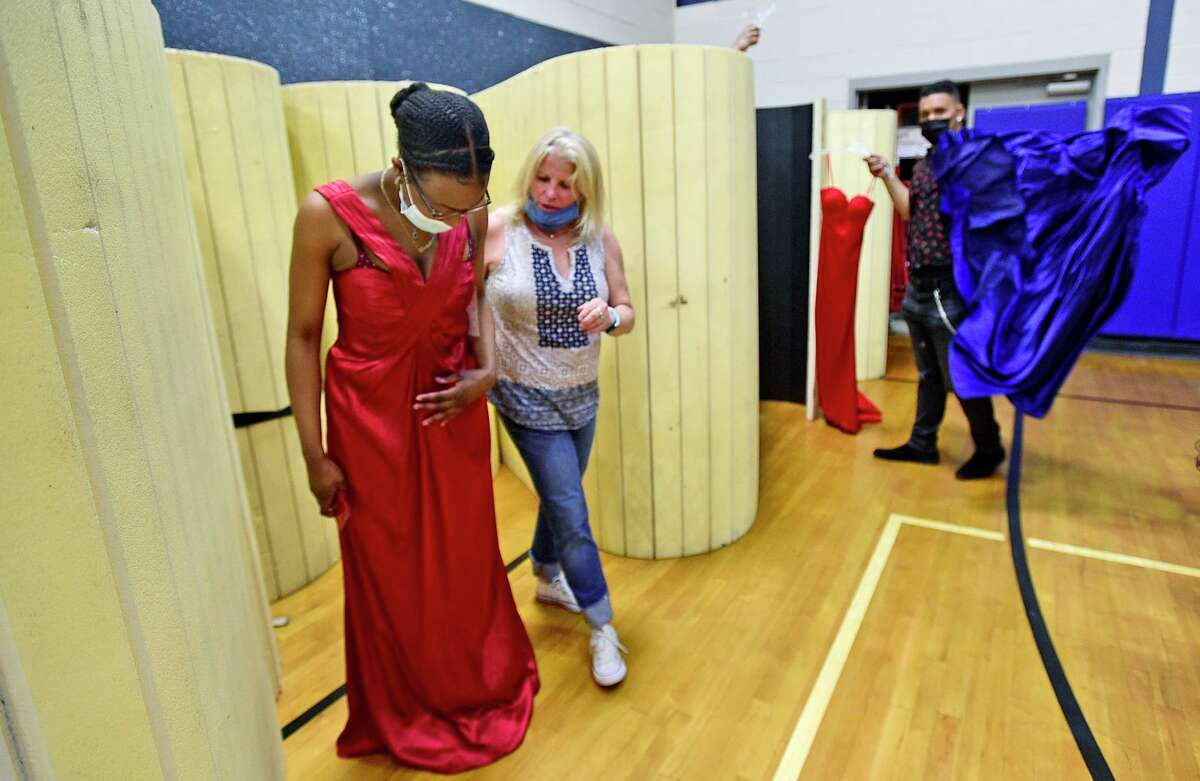 Christi Leveille, a senior at Westhill High School, shops for a dress with the help of volunteer Lynn Cloatrella during The Cinderella Project prom dress giveaway event Friday, May 14, 2021, at the Boys and Girls Club in Stamford. In years prior, the organization would charge about $20 for a dress, but this year, the dresses are free of charge including shoes, jewelry and makeup.