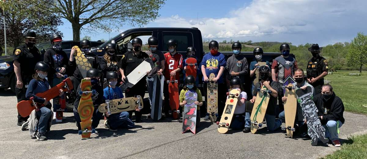 Sixteen Fort Plain eighth-graders were presented with helmets, stickers and safety advice for their longboard skateboard project May 14 by Montgomery County Sheriff Jeffery T. Smith at a ceremony in Wiles Park. Certificates were also handed out to their technology teachers, Kreig Heroth and Ted Arndt. Smith, in turn, was presented with his own custom-made longboard, complete with an emergency beacon. The teachers said it was a culmination of all that they - both faculty and students - learned during the project. Helmeted tudents road-tested their longboards in the park, experimenting with standing and seated rides and gaining confidence and skill with each ride. Arndt and Heroth said that earlier in the year, they thought it would be exciting for the students to build the longboards as a class project. Unlike typical street boards, longboards are used for gracefully cruising around town, or on the bike path. They are 38 to 45 inches long with a correspondingly long wheelbase. The students worked on the project over several months.