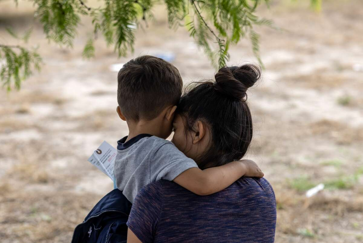 LA JOYA, TEXAS - APRIL 11: A mother and son, 3, from El Salvador wait to be transported to a processing center by U.S. Border Patrol agents after crossing the border from Mexico on April 11, 2021.