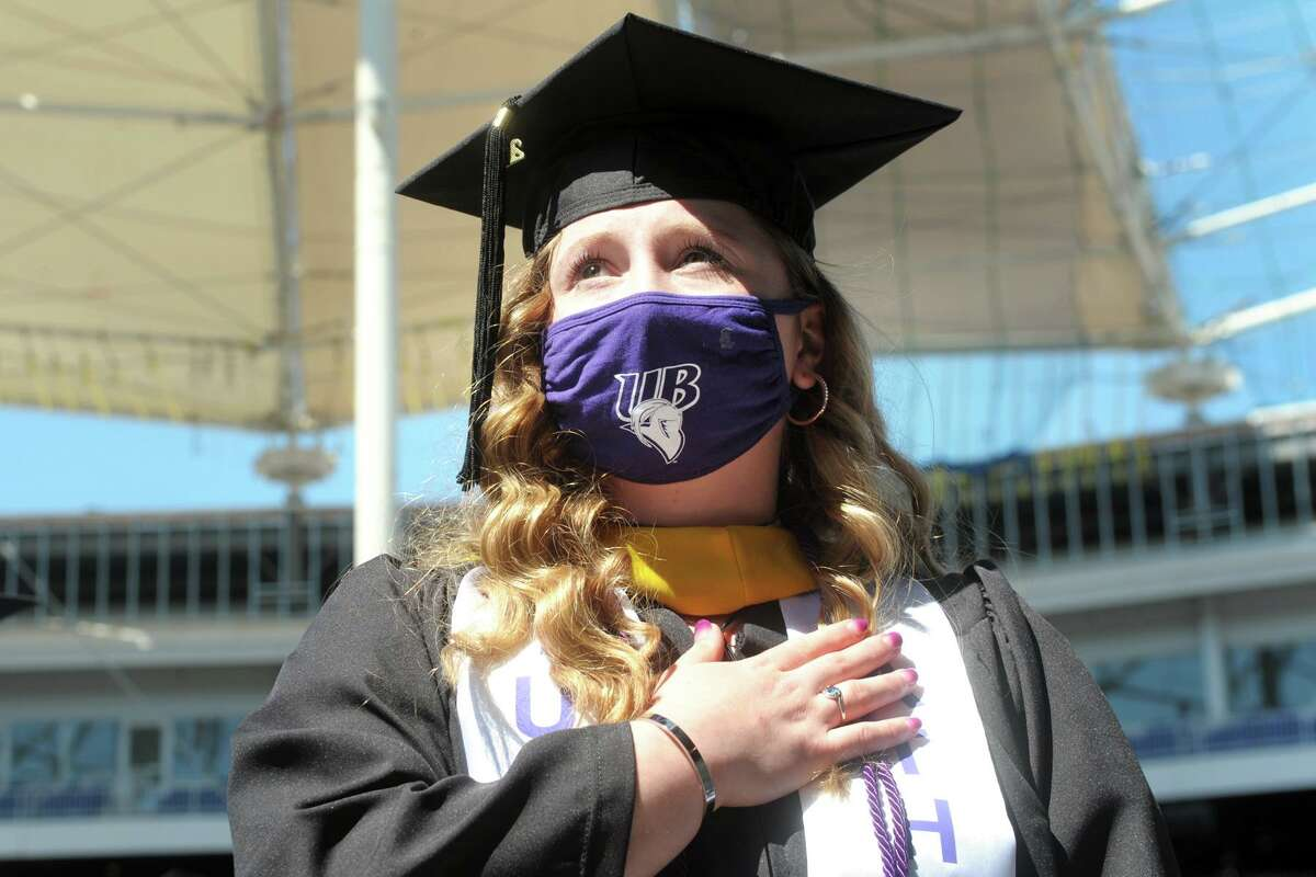 Graduate Gabrielle Kistler stands during the playing of the National Anthem during undergraduate commencement for the University of Bridgeport Class of 2021, at the Hartford Healthcare Amphitheater in Bridgeport, Conn. May 15, 2021.