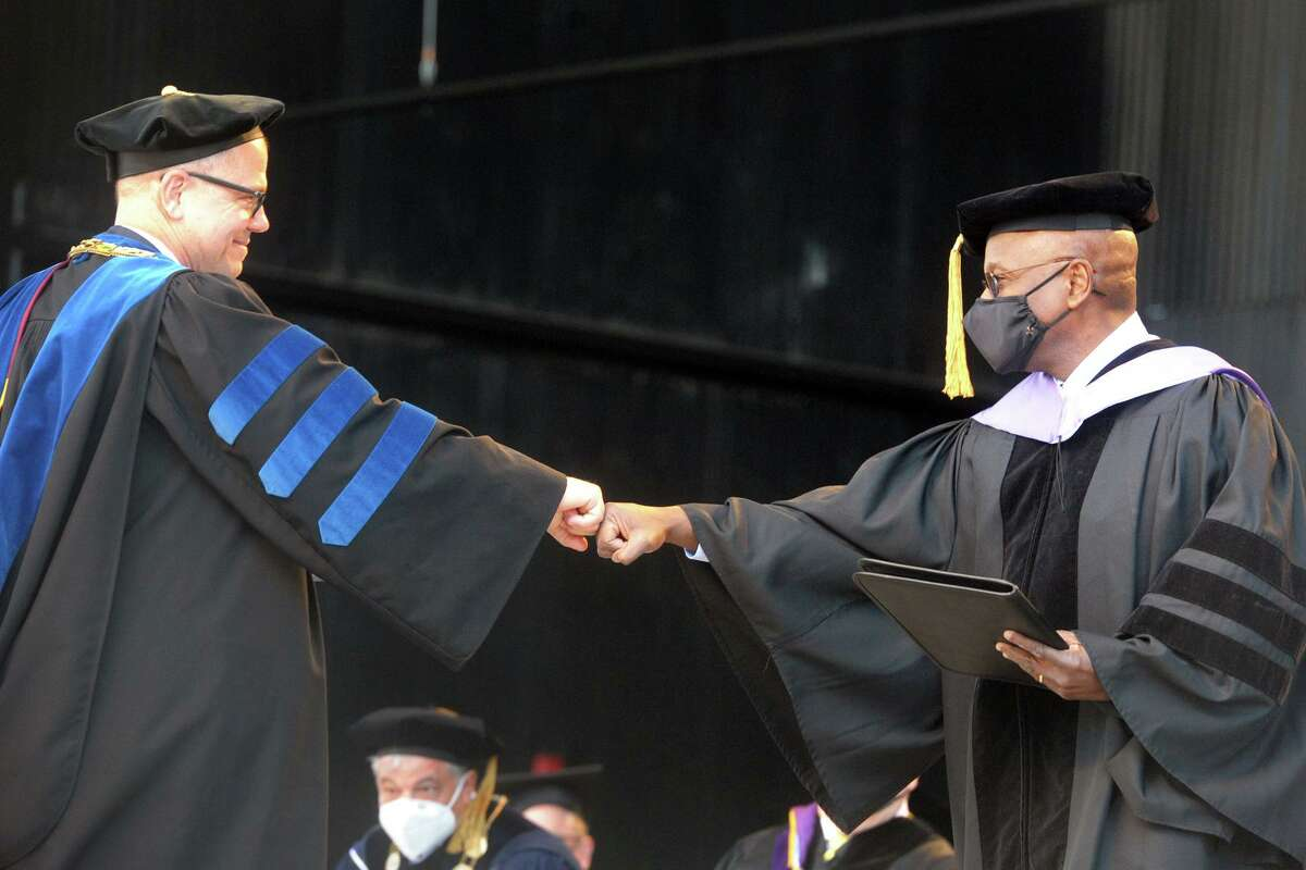 University of Bridgeport President Stephen Healey, left, greets Chief Justice Richard Robinson of the Connecticut Supreme Court during undergraduate commencement for the university's Class of 2021, at the Hartford Healthcare Amphitheater in Bridgeport, Conn. May 15, 2021. Robison received an honorary degree and delivered the commencement address.