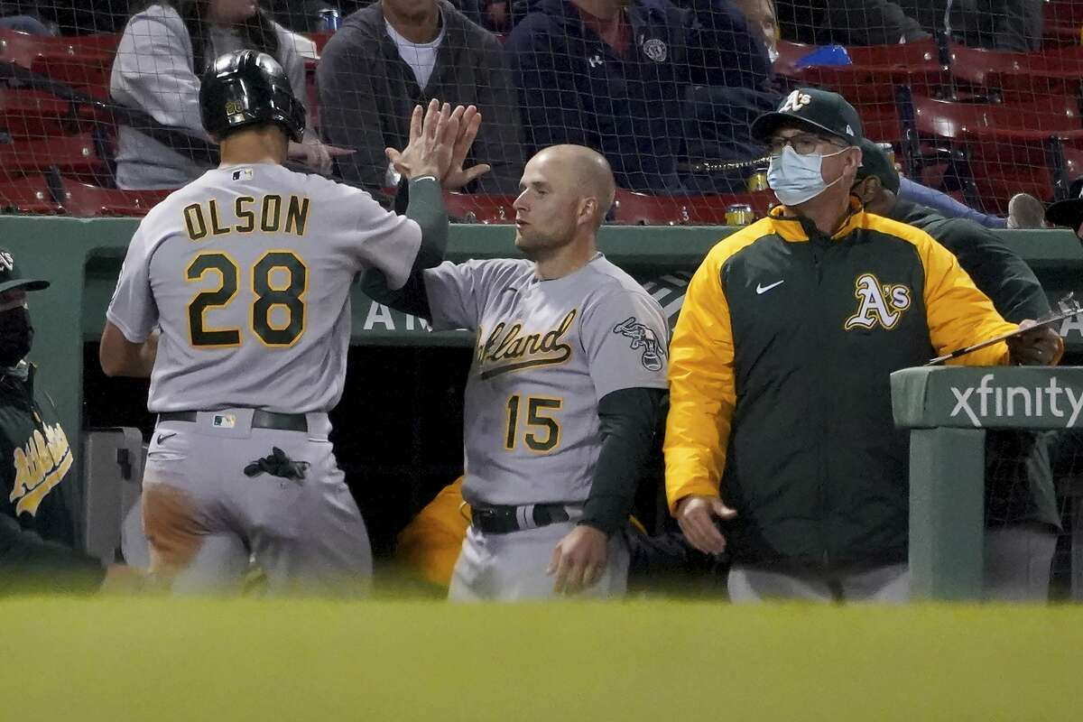 Oakland Athletics' Matt Olson (28) is congratulated at the dugout by Seth Brown (15) after scoring on a hit by Matt Chapman during the seventh inning of a baseball game against the Boston Red Sox, Tuesday, May 11, 2021, in Boston. (AP Photo/Mary Schwalm)
