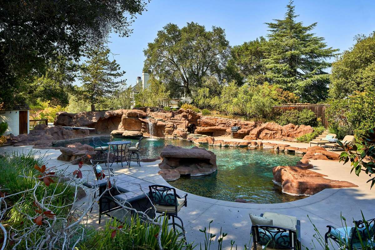 The estate includes this lagoon-like swimming pool, surrounded by trees.