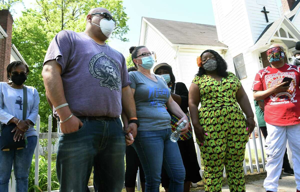 Cathy Foster-Mendez, center, mother of deceased New Haven Firefighter Ricardo Torres Jr., speaks to the press following a prayer vigil in front of Pitts Chapel Unified Free Will Baptist Church in New Haven May 15, 2021. At left is Torres' stepfather, Armand Mendez.