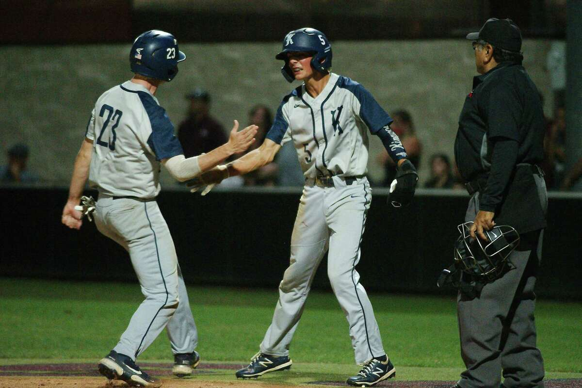 Kingwood's Paxton Singleton (23) and Kingwood's Connor Johnson (5) celebrate after scoring runs against Pearland Thursday, May 13 at Pearland High School.
