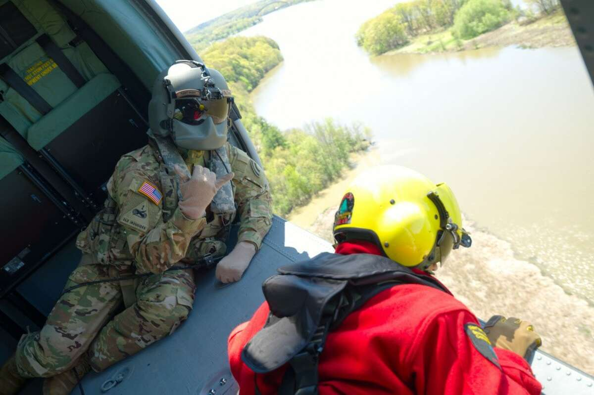 Staff Sgt. Jake Pratta, left, a helicopter crew chief, and a state Department of Environmental Conservation ranger, prepare to deploy during a wildfire exercise.