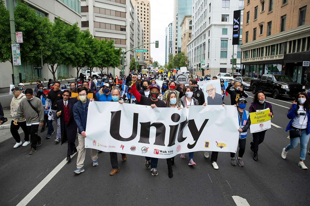 Supporters carry a large Unity banner as they march down Webster Street during the Unite Against Hate March and Rally in Oakland, Calif. on May 15, 2021.