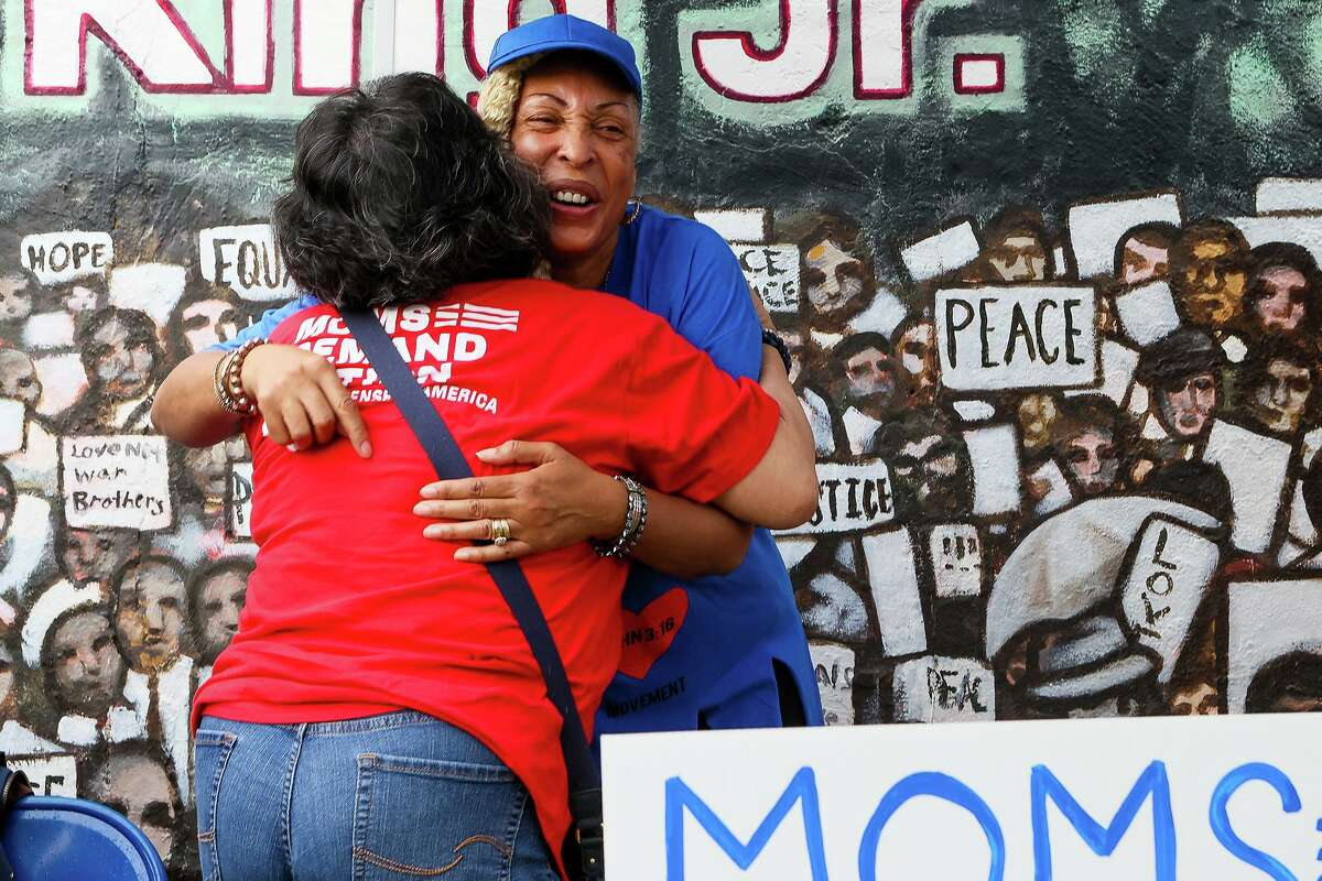 Rosa Wilson, right, bishop of the Greater Faith Institutional Church, receives a hug from Patricia Castillo, with Moms Demand Action for Gun Sense in America, at a rally to highlight the need for healing and action on gun violence prevention outside the church Sunday, May 15, 2021.