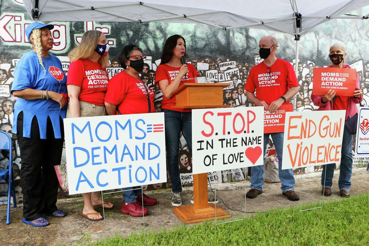Cori Ferraro, a volunteer with the Bexar County group of Moms Demand Action for Gun Sense in America, speaks at Sunday's rally. Standing with her are, from left, Rosa Wilson, bishop of the Greater Faith Institutional Church; Gail Reinhart; Patricia Castillo; Mike Munroe; and Pauline Howard.