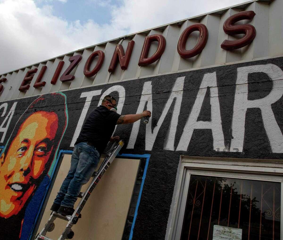 Alexandro Gonzalez-Hernandez paints a mural depicting Elon Musk in downtown Brownsville.