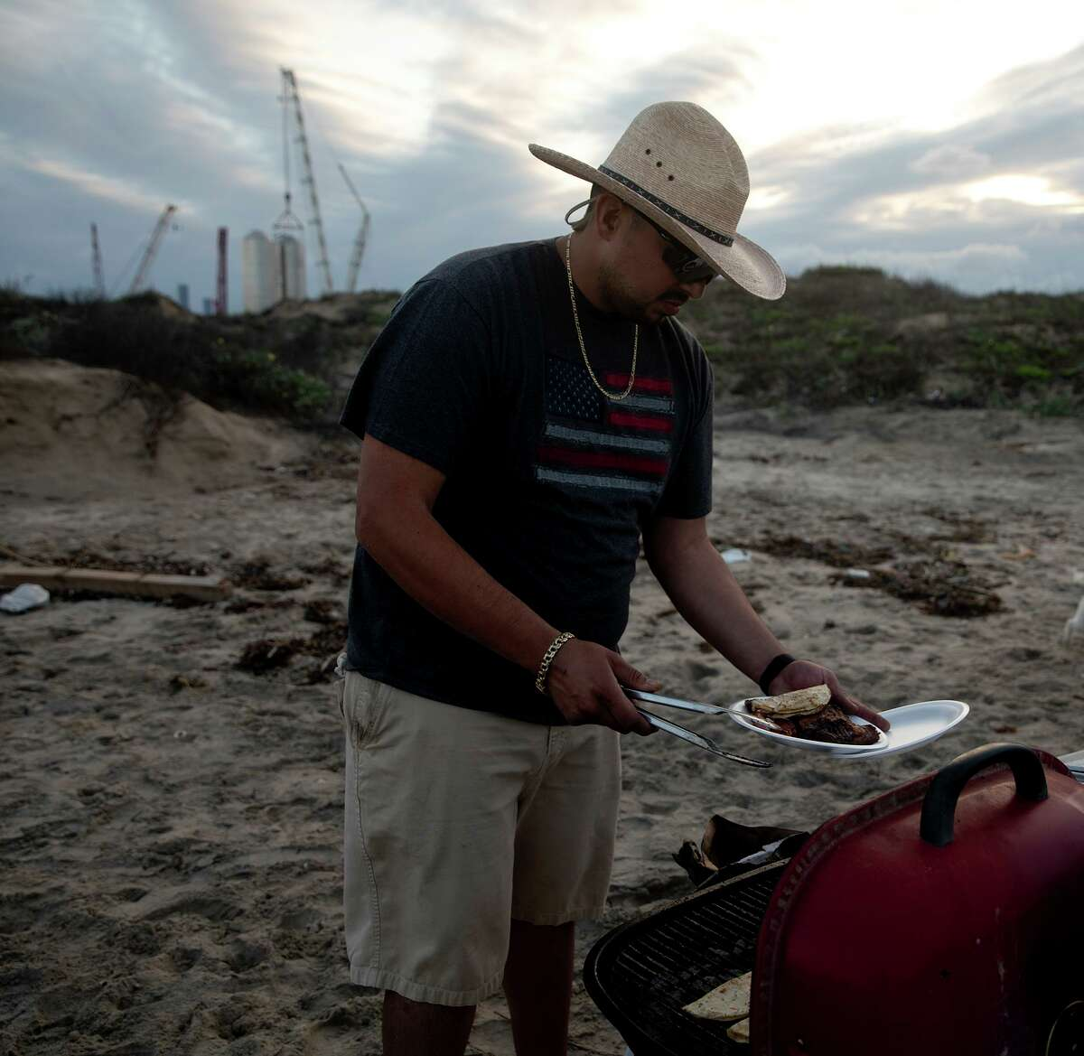 Jesus Chavez plates his food while his daughter Brianna Chavez wander behind him. The family came to Boca Chica beach to celebrate Brianna?•s 16th birthday. They were forced to wait on Highway 4, the only way into the beach, because SpaceX was moving equipment. Road closures from the space facility are common.