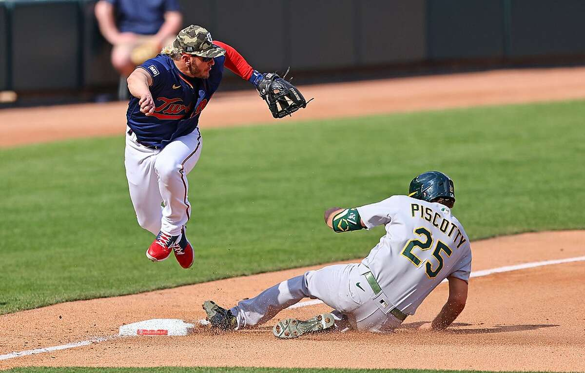 MINNEAPOLIS, MINNESOTA - MAY 15: Josh Donaldson #20 of the Minnesota Twins jumps out of the way of Stephen Piscotty #25 of the Oakland Athletics in the fifth inning against the Minnesota Twins at Target Field on May 15, 2021 in Minneapolis, Minnesota.(Photo by Adam Bettcher/Getty Images)