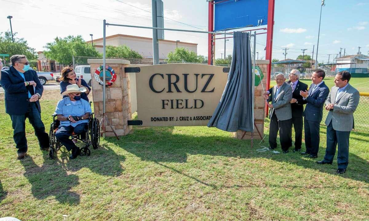 Robert Cruz, Diana Cruz, Manuel Cruz, Felix Cruz, Conrado Cruz, Juan Cruz and Laredo City Councilmember Albert Torres gather to unveil the Cruz Field monument, Friday, May 14, 2021, during a ceremony.